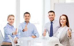 Happy team of architects and designers in office. Business, architecture and office concept - happy team of architects and designers in office showing thumbs up Royalty Free Stock Image