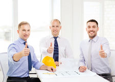 Happy team of architects and designers in office. Business, architecture and office concept - happy team of architects and designers in office showing thumbs up Stock Photos