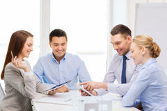 Happy team of architects and designers in office. Business, technology, architecture and office concept - happy team of architects and designers in office with Stock Image