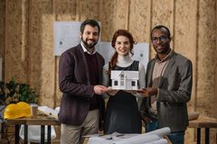 Happy team of architects holding miniature model of building. At office royalty free stock photography