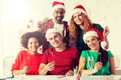 Happy team celebrating christmas at office party. Christmas, celebration and holidays concept - happy team in santa hats with sparklers and non-alcoholic royalty free stock image
