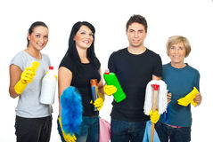 Happy team of cleaning house workers. Happy team of cleaning workers holding cleaning products and their equipment and offering professional cleaning services royalty free stock images