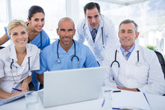 Happy team of doctors looking at camera in behind laptop computer Stock Photos