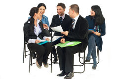 Happy team having conversation at seminar. Happy team of five business people sitting on chairs and having funny conversation at seminar isolated on white Royalty Free Stock Photos
