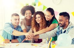 Happy team at office party holding hands together royalty free stock photo