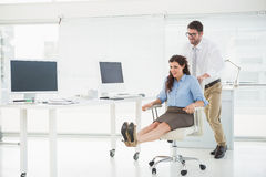 Happy team playing together with swivel chair Stock Photo