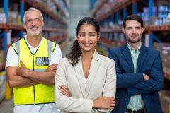 Happy team is smiling and posing with crossed arms. In a warehouse Stock Photo