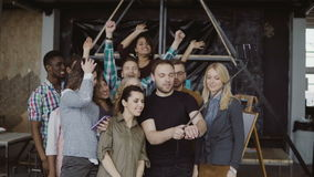 Happy team takes selfie at loft office. Man holds smartphone with self-stick and takes photo of workers, smiling friends stock footage
