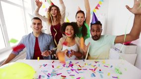 Happy team throwing confetti at office party. Corporate, celebration and holidays concept - happy team throwing confetti and serpentine at office party stock video footage