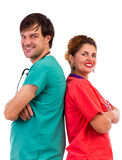 Happy team of two doctors standing back to back with arms folded. Isolated on white background Stock Photography