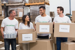 Happy team of volunteers holding donations boxes. In a large warehouse Stock Photography