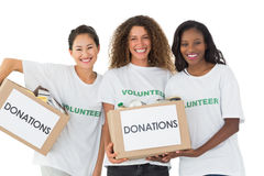 Happy team of volunteers smiling at camera holding donations boxes. On white background stock image