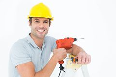 Happy technician holding drill machine while leaning on ladder. Portrait of happy technician holding drill machine while leaning on step ladder Stock Images