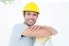 Happy technician leaning on step ladder Royalty Free Stock Image