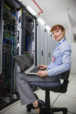 Happy technician sitting on swivel chair using laptop to diagnose servers Stock Photos
