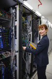 Happy technician using digital cable analyzer on server Stock Image