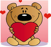 Happy teddy bear holding a red heart Stock Image