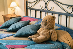 Happy teddy bear. Relaxing on comfortable bed Stock Image