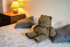 Happy teddy bear. Relaxing on comfortable bed Royalty Free Stock Photography