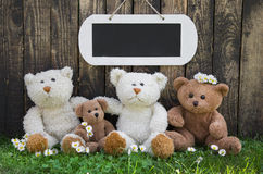 Happy teddy bear team on wooden background for a greeting card w Royalty Free Stock Photos