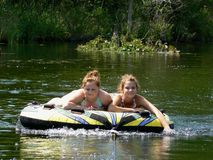 Happy Teen Best Friends River Tubing. My teenage daughter and her friend relaxing on a tube (and posing) on a lazy ride down the river behind our boat on a Stock Image