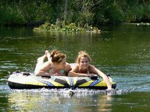 Happy Teen Best Friends River Tubing. My teenage daughter and her friend relaxing on a tube (and posing) on a lazy ride down the river behind our boat on a Royalty Free Stock Photos