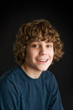 Happy teen boy. Closeup of a happy teen boy shot in studio on a black background Royalty Free Stock Photography