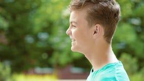 Teen boy drinking water outdoors stock video footage