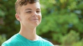 Teen boy drinking water outdoors stock footage