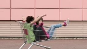 Happy family with shopping carts. Happy teen boy and girl is riding in shopping carts in a parking lot near a supermarket. Young friends children having fun stock footage