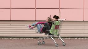 Happy family with shopping carts. Happy teen boy and girl is riding in shopping carts in a parking lot near a supermarket. Young friends children having fun stock video footage