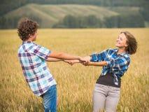 Happy teen boy and girl walking in a rye field Stock Photo