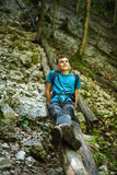 Happy teen boy hiker. Happy teenager sitting on a log, resting after hiking on a forest trail Stock Photo