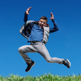 Happy teen boy jumping on meadow. Happy teen boy jumping on grass hill against clear sky background Stock Photos