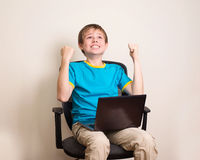 Happy teen boy with laptop in winning pose. Success kid in offic. E chair with portable pc happy ecstatic celebrating being a winner Royalty Free Stock Photos