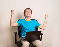 Happy teen boy with laptop in winning pose. Success kid in offic. E chair with portable pc happy ecstatic celebrating being a winner Stock Photography