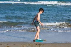 Happy teen boy in the swim flippers having fun on the sand оn the beach stock images