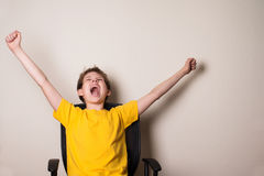 Happy teen boy in winning pose hands up shouting. Success kid ha. Ppy ecstatic celebrating being a winner Stock Photo