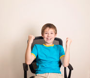 Happy teen boy in winning pose. Success kid in office chair happ. Y ecstatic celebrating being a winner Stock Image
