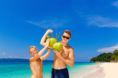 Happy teen boys having fun on the tropical beach with a bunch of. Coconuts. Summer vacation concept Royalty Free Stock Photo