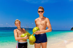 Happy teen boys having fun on the tropical beach with a bunch of. Coconuts. Summer vacation concept Stock Image