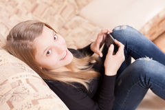 Happy teen with cellphone sitting on the sofa in the living room Royalty Free Stock Photos