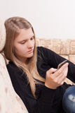 Happy teen with cellphone sitting on the sofa in the living room Stock Images