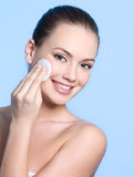 Happy teen with cotton swab cleaning face Royalty Free Stock Images