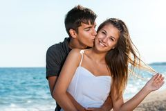 Happy teen couple embracing on beach. Stock Photo