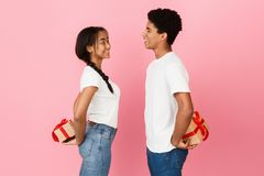 Happy teen couple hiding gift boxes behind backs. Over pink background, side view stock images