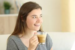 Happy teen drinking coffee with milk looking at side Royalty Free Stock Photo