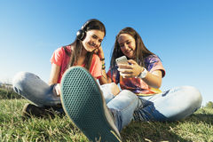 Happy teen friends in summer park listening music. Stock Image