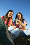 Happy teen friends in summer park listening music. Royalty Free Stock Photography