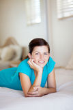 Happy teen girl. Lying on her bed at home Royalty Free Stock Images